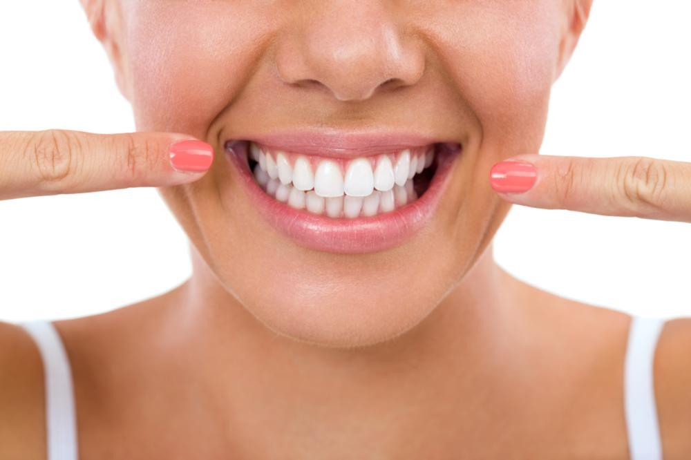 woman pointing to her teeth | teeth whitening wausau wi